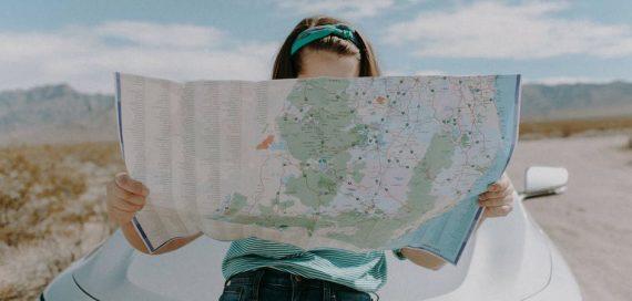 menina de azul olhando para uma mapa