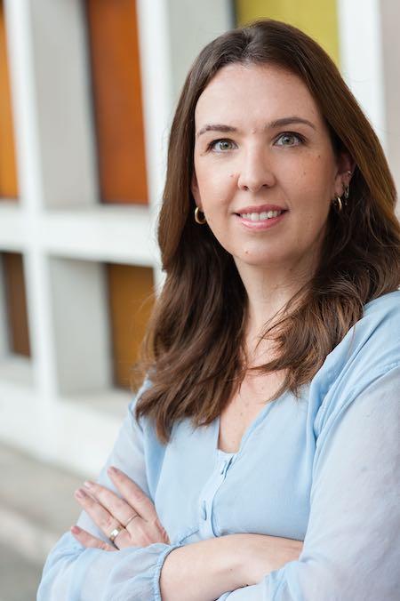 Marília Carvalhinha, uma mulher de cabelo castanho, de blusa azul claro com braços cruzados