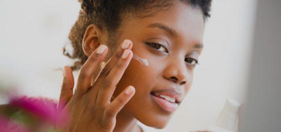 Mulher negra aplicando creme no rosto