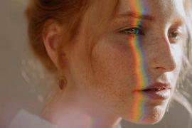 Mulher branca de4 cabelo claro com arco iris no rosto