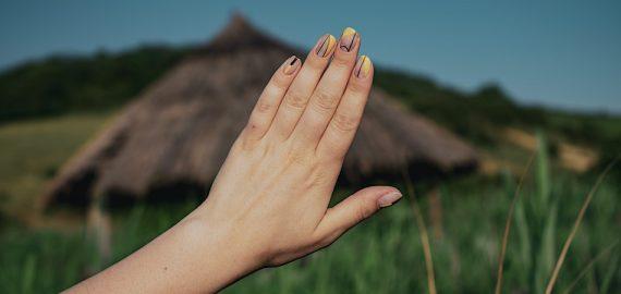 mão de uma mulher de unhas pintadas no campo