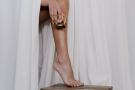Mulher passando um body brush na perna