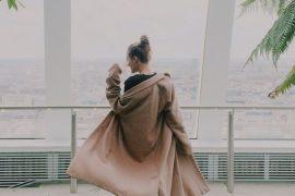 mulher branca de cabelo loiro e casaco bege olhado por uma janela grande