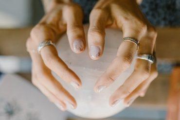 ma~e de mulher branca com aneis segurando uma bola de cristal
