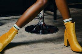 perna de uma mulher negra usando bota amarela